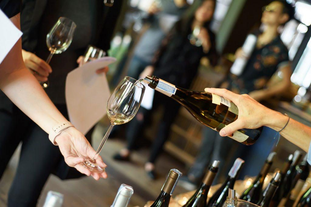 Serveur tient une bouteille de vin et verse un verre de vin aux visiteurs du salon VinOmed